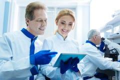 Üppige Forscher, welche die Tablette betrachten Stockbilder