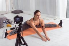 Üppige Frau, die Übungen für ihr Blog tut Stockfotografie