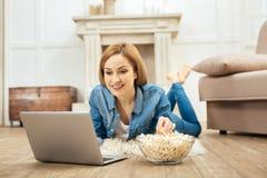 Üppige Frau, die auf dem Boden liegt und Popcorn isst Lizenzfreie Stockfotografie