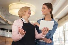 Üppige Kellnerin, die Menü mit ihrem Arbeitgeber bespricht Lizenzfreie Stockbilder