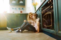 Üppige Mutter und Tochter, die auf dem Boden sitzt Stockfotografie
