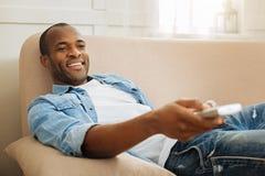 Üppiger Mann, der auf dem Sofa stillsteht stockbild