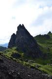 Üppiges grünes Lanscape mit Berggipfel-Felsen stockfoto