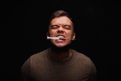 Ćpun z narkomaniami zaciska między zębami strzykawkę z injectable lekiem na ciemnego czerni tle zdjęcia royalty free