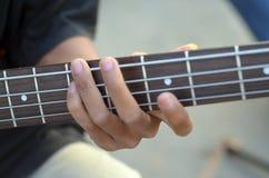 Ćwiczyć w bawić się basową gitarę Zakończenie up mężczyzna ręka bawić się basową gitarę Zdjęcia Stock