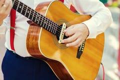 Ćwiczyć w bawić się gitarę Przystojni młodzi człowiecy bawić się gitarę, Zdjęcia Stock