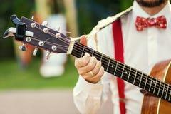 Ćwiczyć w bawić się gitarę Przystojni młodzi człowiecy bawić się gitarę, Zdjęcie Stock