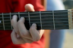 Ćwiczyć w bawić się gitarę Zamyka up mężczyzna ręka bawić się gitarę Fotografia Royalty Free