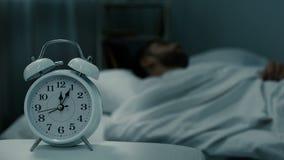 Łóżka dosypiania zegarowy pokazuje midnight pobliski mężczyzna w łóżku, spoczynkowe godziny, zdrowy sen zbiory