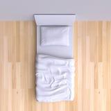 Łóżko z poduszką i koc w narożnikowym pokoju Zdjęcie Stock