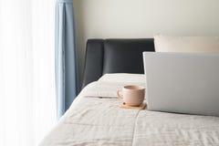 Łóżko z ranek kawą i tylni widokiem laptopu ekran w sypialni obraz royalty free