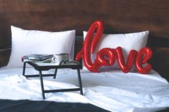Łóżko z tacą i balonem w formie słowo miłości zdjęcie stock