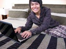łóżkowego laptopu relaksujący potomstwa Obraz Royalty Free