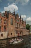 Łódź i ceglani domy na kanałowym ` s ostrzymy przy Bruges Obrazy Stock