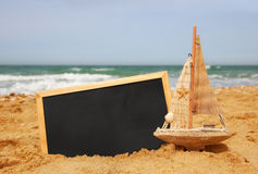 Łódź i chalkboard, na dennym piasku i oceanu horyzoncie Fotografia Royalty Free
