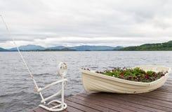 Łódź jako kwiatu garnek i żelazo rybak na molu na jeziorze obraz royalty free