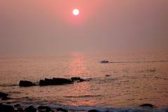 Łódź motorowa pływa statkiem na morzu który odbija wibrującego pomarańczowego koloru żółtego kolor położenia słońce obraz royalty free