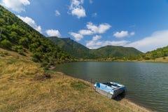 Łódź na jeziorze na montains tle Zdjęcie Stock