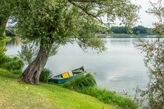 Łódź na jeziorze pod drzewem Obrazy Royalty Free