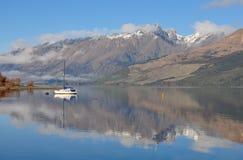 Łódź na jeziorze z halnym odbiciem w Glenorchy, Nowy Zealan Zdjęcie Royalty Free
