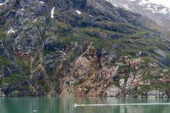 Łódź na oceanie z Halnym tłem i chmurnym niebem przy lodowiec zatoką Alaska fotografia royalty free