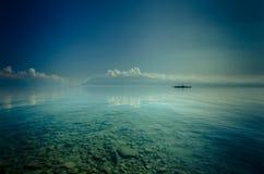 Łódź na przejrzystym jeziorze nawadnia Zdjęcia Stock