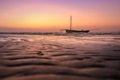 Łódź na tropikalnej plaży przy zmierzchem lub wschodem słońca Zdjęcia Stock