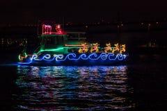 Łódź Ozdabiająca z Bożenarodzeniowymi wakacji światłami, Święty Mikołaj sanie, renifer i odbicie w wodzie, obraz royalty free