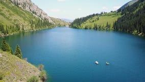 Łódź po środku halnego jeziora Krajobrazowy halny jezioro w lesie zbiory