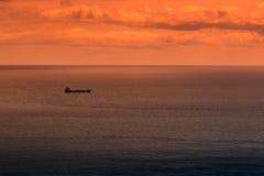 Łódź przy morzem na horyzoncie przy zmierzchem Zdjęcia Royalty Free