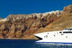Łódź przy wysoką powulkaniczną falezą Santorini wyspa Zdjęcia Royalty Free