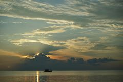 Łódź przy zmierzchem i wschód słońca z dramatycznym niebem nad oceanem zdjęcia royalty free