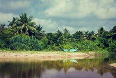 Łódź rybacka na tropikalnej plaży z drzewkami palmowymi w backgrou zdjęcia royalty free
