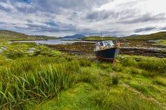 Łódź rybacka na ziemi w malowniczym środowisku przed wpustem przy niskim przypływem w krajobrazie ` wyspa Harris i Lew zdjęcia royalty free