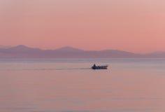 Łódź rybacka przy wschodem słońca w morzu Obrazy Royalty Free