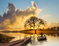 Łódź rybacka przy zmierzchem na pięknym jeziorze zdjęcia stock
