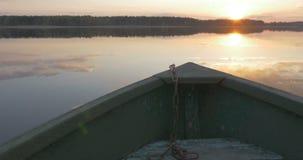 Łódź unosi się na jeziorze przy zmierzchem zbiory