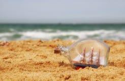 Łódź w butelce na dennym piasku i oceanu horyzoncie Zdjęcie Royalty Free