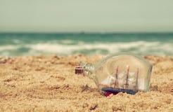 Łódź w butelce na dennym piasku i oceanu horyzoncie Zdjęcia Royalty Free