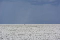 Łódź w morzu na horyzoncie, niebieskie niebo Zdjęcia Stock