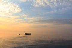 Łódź w oceanie przy wschodem słońca Obrazy Royalty Free