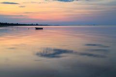Łódź w oceanie przy wschodem słońca Zdjęcia Stock