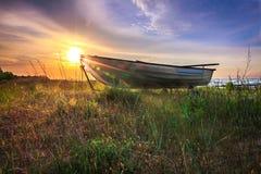 Łódź w trawie z wschodem słońca Obraz Stock