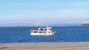 Łódź z turystami żegluje na morzu przeciw tłu góry w Gruzja, Batumi zbiory