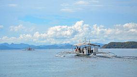 Łódź z turystami unosi się na morzu mgliste góry na horyzoncie zdjęcia royalty free