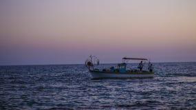 Łódkowaci rybacy unosi się w morzu przy zmierzchem rybacy zbierają ich sieci handlowych statków sylwetka Obrazy Stock