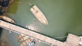 Łódkowata pozycja w parking blisko drewnianego mola na zielonym jeziornym widok z lotu ptaka Drewniane łodzie na parking w rzeczn zbiory wideo