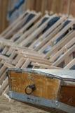 Łódkowaty ogon drewniana wioślarska łódź w tle i serie zawieszeni puści deckchairs wykładali up w rozkazie na plaży Zdjęcie Stock