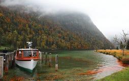 Łódkowaty parking na Jeziornym Konigssee z drewnianym molem i spadać liśćmi brzeg jeziora na mglistym mgłowym ranku Fotografia Royalty Free