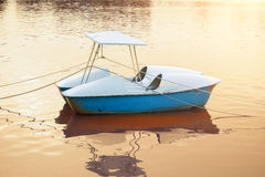 Łódkowaty unosić się nad skóry wodą z lekkim przeciekiem od zmierzchu jako bac Zdjęcie Stock